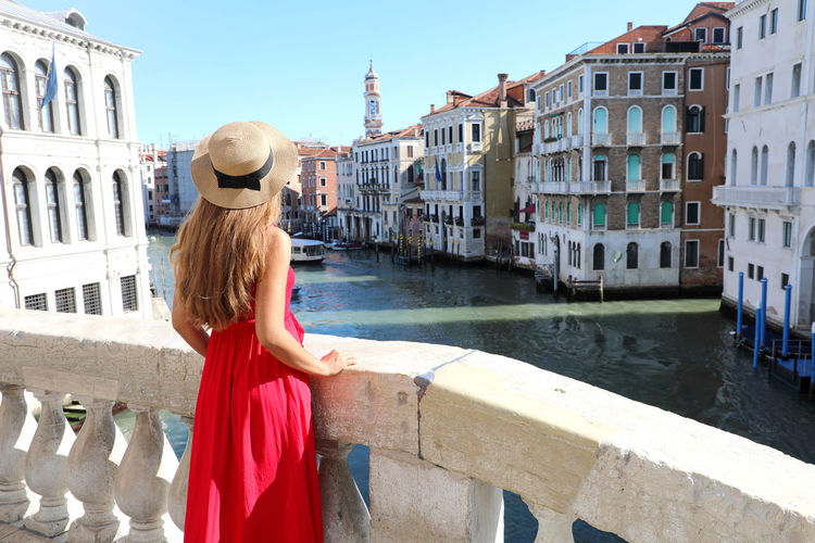 Woman standing by canal against buildings in city
