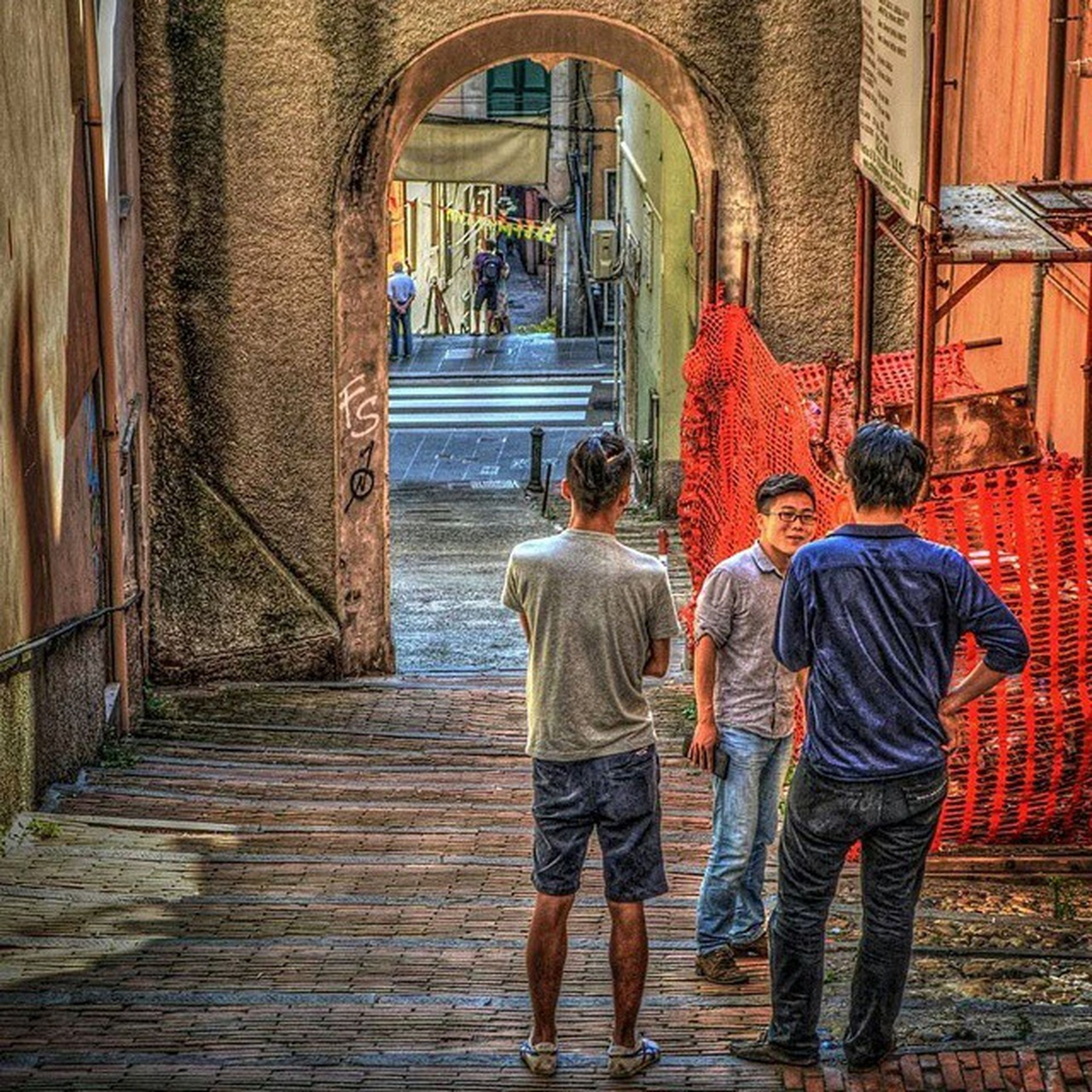 architecture, built structure, building exterior, full length, lifestyles, men, rear view, person, casual clothing, leisure activity, walking, standing, togetherness, arch, building, boys, bonding, window