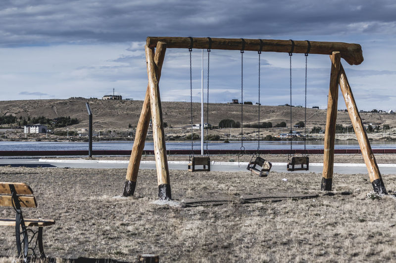 Empty swing in playground against sky during winter