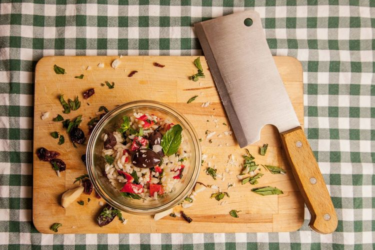 Directly above view of rice and vegetables in bowl by meat cleaver on cutting board