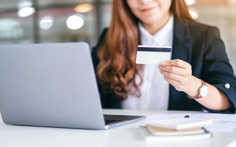 Midsection of woman using laptop while holding credit card over table