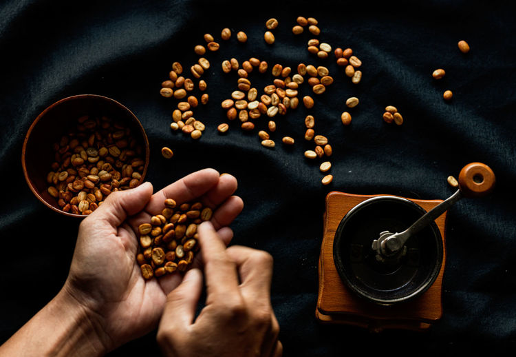 High angle view of hands holding coffee beans on table