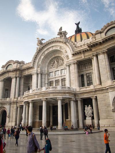 Tourist outside palacio de bellas artes against sky