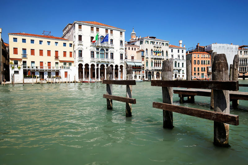 Wooden posts in grand canal against buildings