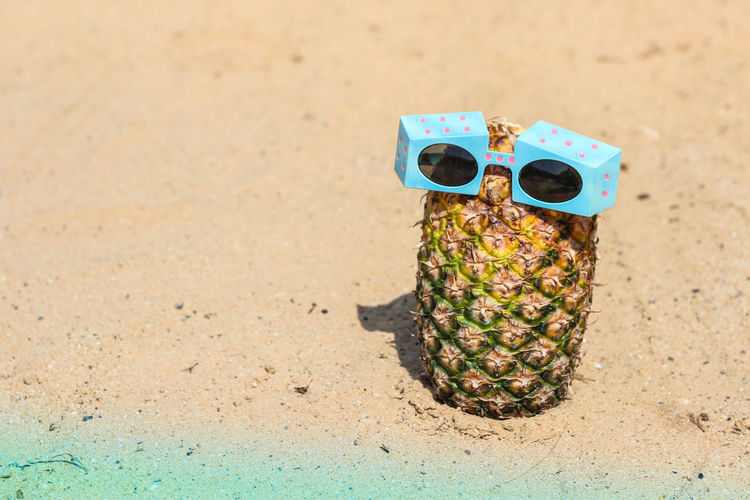 Sunglasses and pineapple on sandy beach