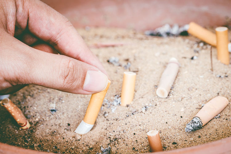 Close-up of hand holding cigarette butt in sand