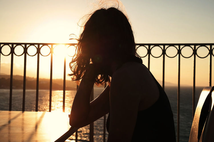 Woman Sitting On Chair At Table Against Sky During Sunset