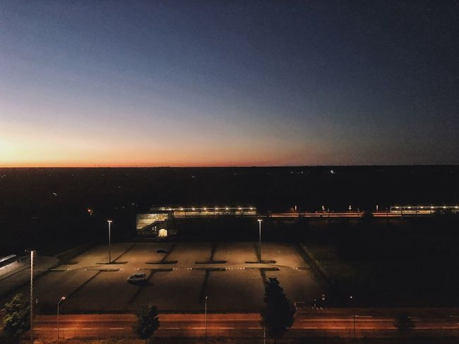 I stayed at work a bit too long. View of the station from our office window. HUAWEI Photo Award: After Dark View Dawn Sunset Parking Lot Train Station Sky Water Beauty In Nature Night Sunset Illuminated Nature Scenics - Nature Transportation No People Road Dusk Outdoors Tranquility Tranquil Scene Silhouette Street City