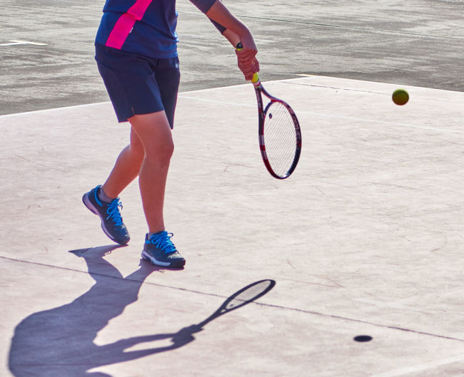 Activity Casual Clothing Child Competitive Sport Court Exercising Healthy Lifestyle Human Body Part Human Leg Lifestyles Low Section One Person Playing Racket Red Serving - Sport Shoe Skill  Sport Sports Training Standing Sunlight Tennis Tennis Racket Vitality