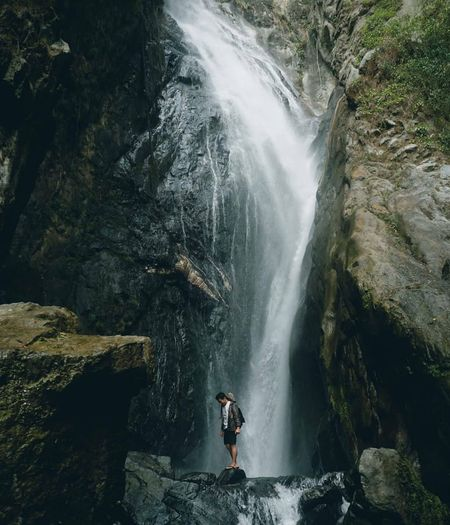 Full length of man standing by waterfall