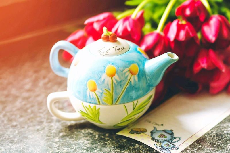 Close-Up Of Teapot With Flowers On Table
