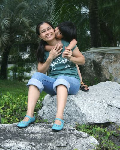 Portrait of happy mother and boy sitting on rock against trees
