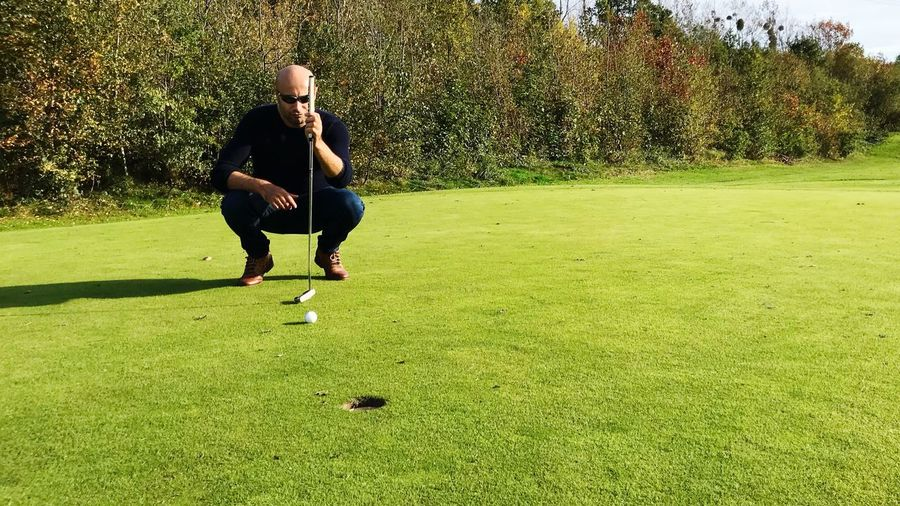 Full length of man holding club while crouching on golf course