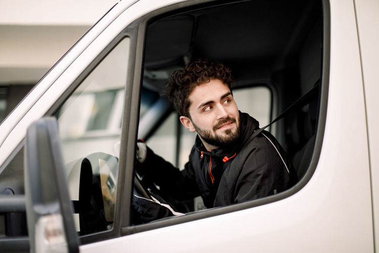 Portrait of young man sitting in car