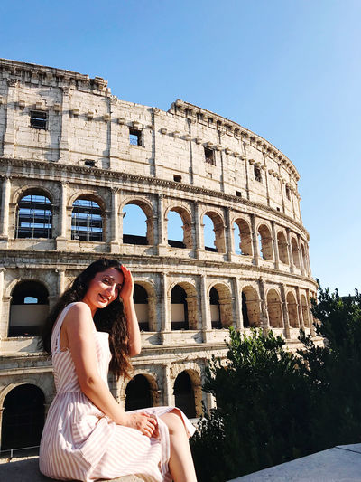 Portrait of smiling woman sitting against historic building during sunny day