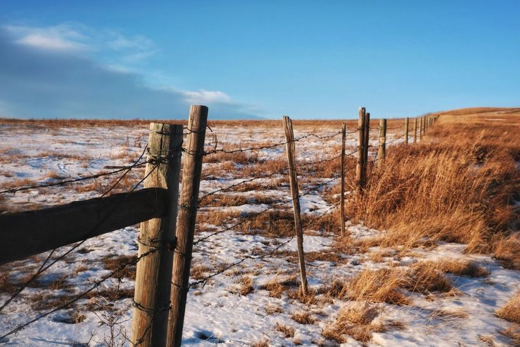 Wooden fence on snow covered field against sky
