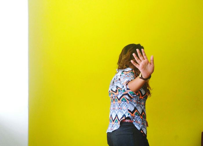 Woman showing stop gesture against yellow wall