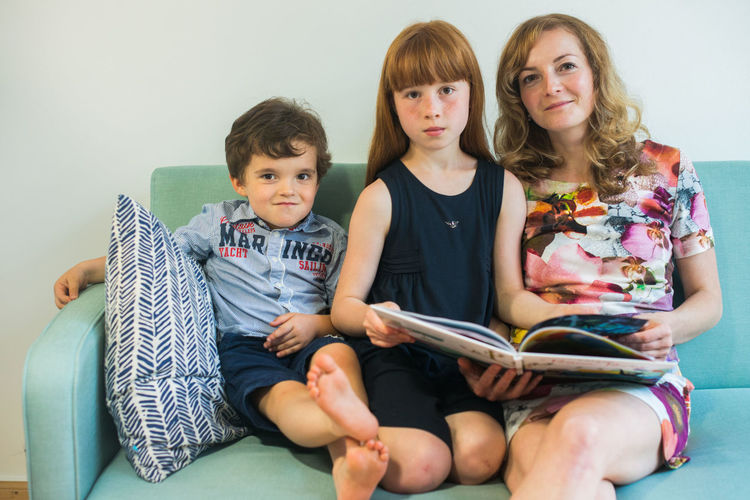 Portrait of mother and children reading book while sitting on sofa at home