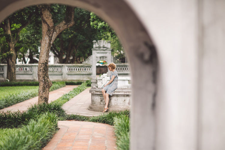 Woman seen through arch in park