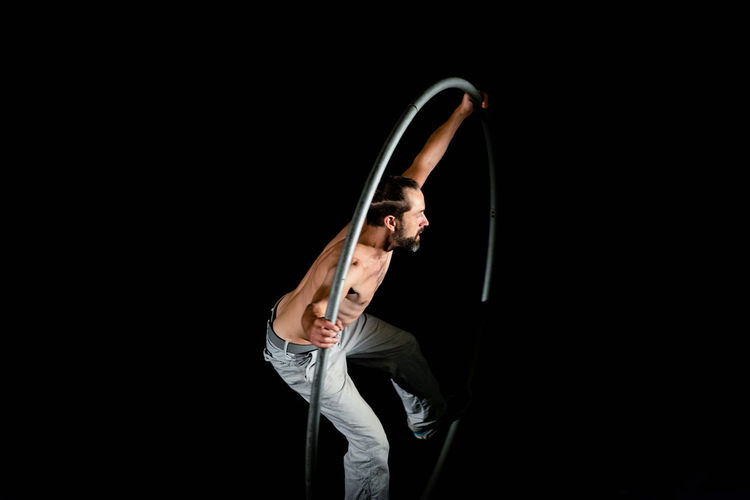 Circus Arms Raised Arts Culture And Entertainment Black Background Copy Space Cut Out Flexibility Holding Indoors  Lifestyles Music One Person Performance Practicing Skill  Stage Standing Studio Shot Three Quarter Length Young Adult Young Men
