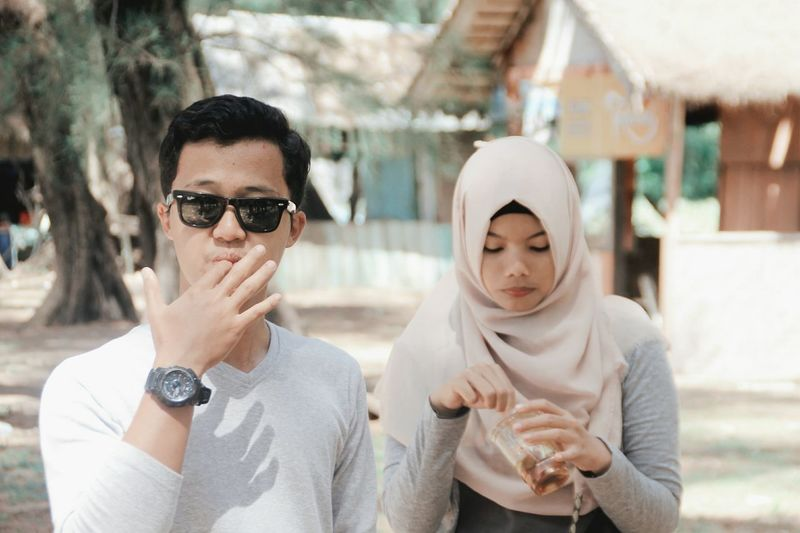 Couple having drink outdoors in sunny day