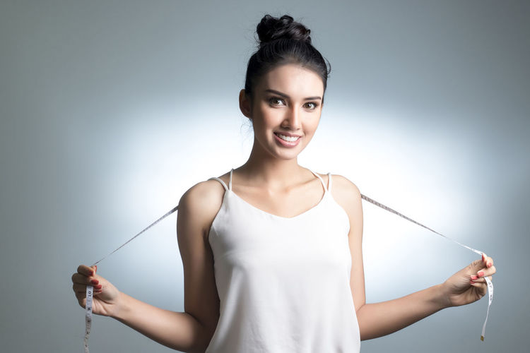 Portrait of smiling young woman standing with tape measure against gray background