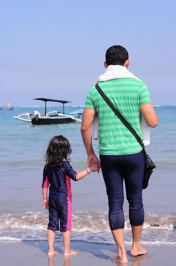 Rear view of father and daughter holding hands while standing at beach against sky
