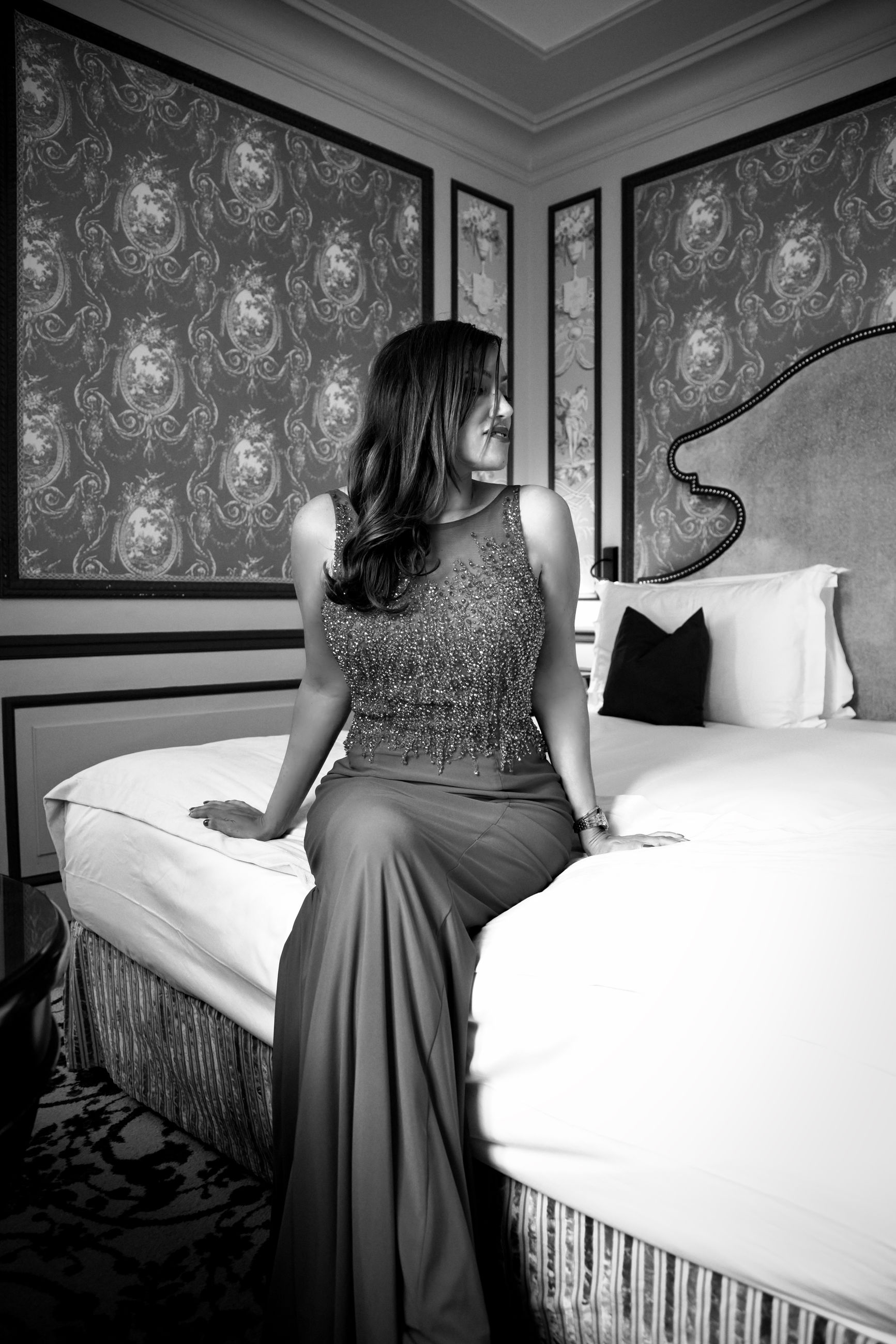 women, adult, black and white, one person, black, indoors, furniture, bed, domestic room, bedroom, dress, monochrome photography, white, lifestyles, monochrome, rear view, luxury, sitting, wealth, female, home interior, young adult, clothing, fashion, full length, hairstyle, elegance, hotel, relaxation, long hair, person, domestic life, window, photo shoot, bride, hotel room, looking