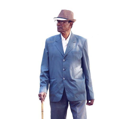 Senior man wearing hat standing against white background
