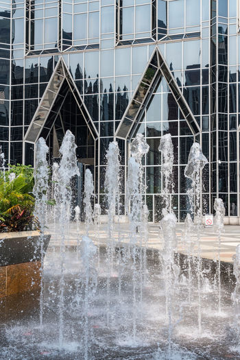 Fountain by building in city