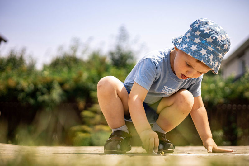Rear view of boy playing with plants