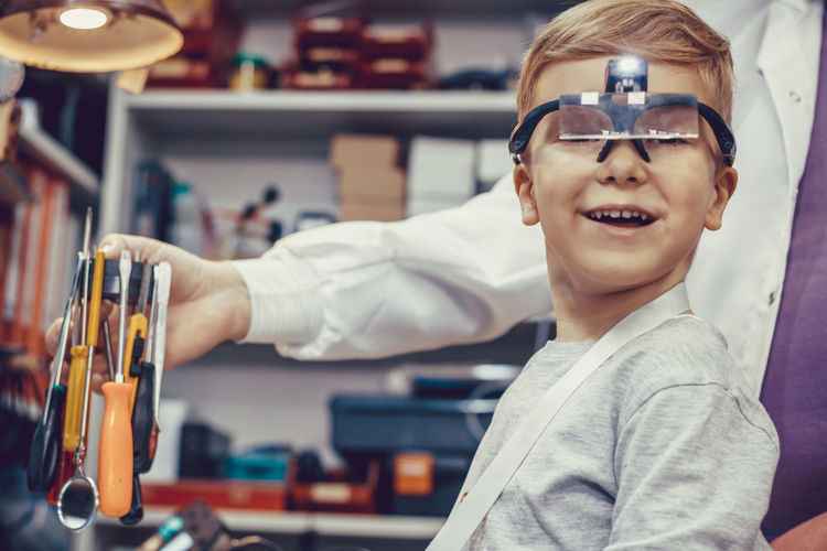 Happy kid with magnifying eyeglasses during physics experiment in engineering lab.