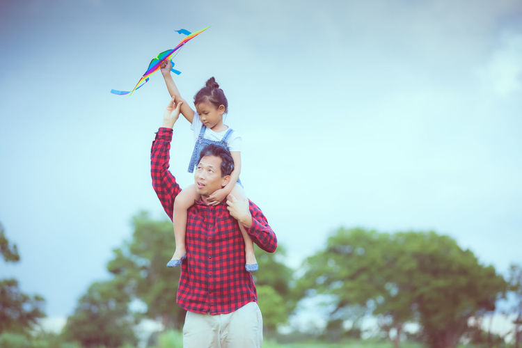 Father carrying daughter on shoulder against sky