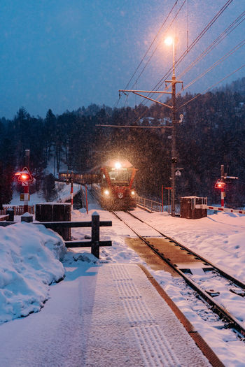 Train approaching in Suiss mountains in winter at night Snow Cold Temperature Winter Illuminated Transportation Mode Of Transportation Street Rail Transportation Railroad Track City Street Light Night Track Lighting Equipment Architecture Nature Tree Dusk Electricity  No People Outdoors Snowing Light Extreme Weather Train