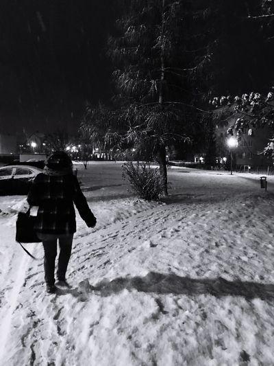 Full length rear view of man walking in snow