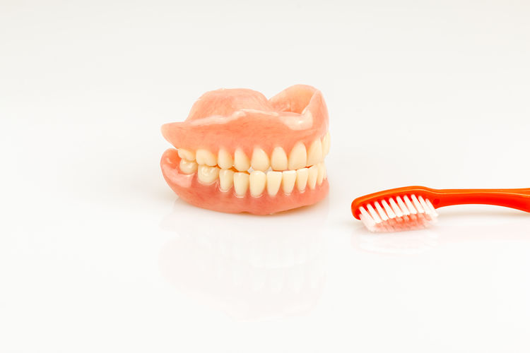 Dentures and a toothbrush on a white background. Care Fake Health Prosthesis Replacement Dental Dentist Dentistry Artificial Close-up Copy Space Cosmetic Dental Health Dentures No People Orthodontist  Studio Shot White Background