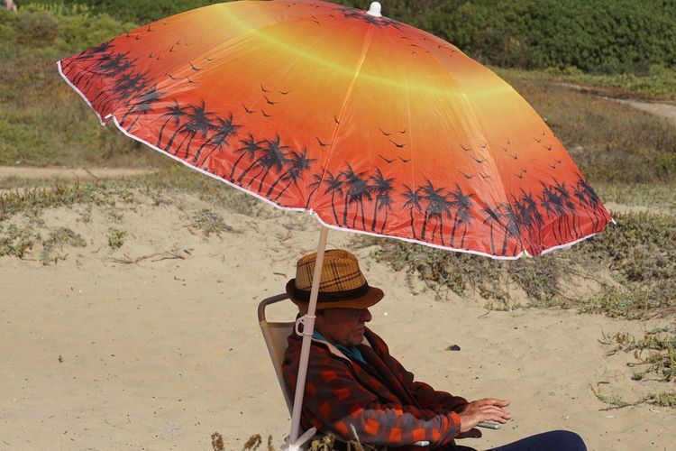 A old men enjoying the afternoon under an umbrella Adult One Person People Environment Adults Only Only Women Outdoors Nature Day