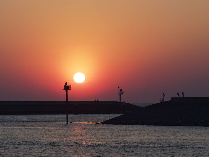 Water Sunset Sky Beauty In Nature Scenics - Nature Sea Orange Color Sun Silhouette Waterfront Nature Tranquil Scene Street Light Tranquility Idyllic Clear Sky Horizon Over Water Outdoors Horizon No People