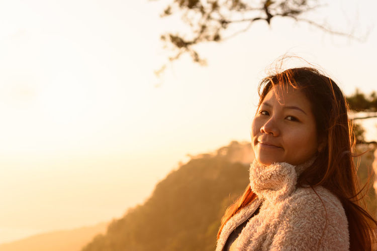 Portrait of young woman looking away against sky during sunset
