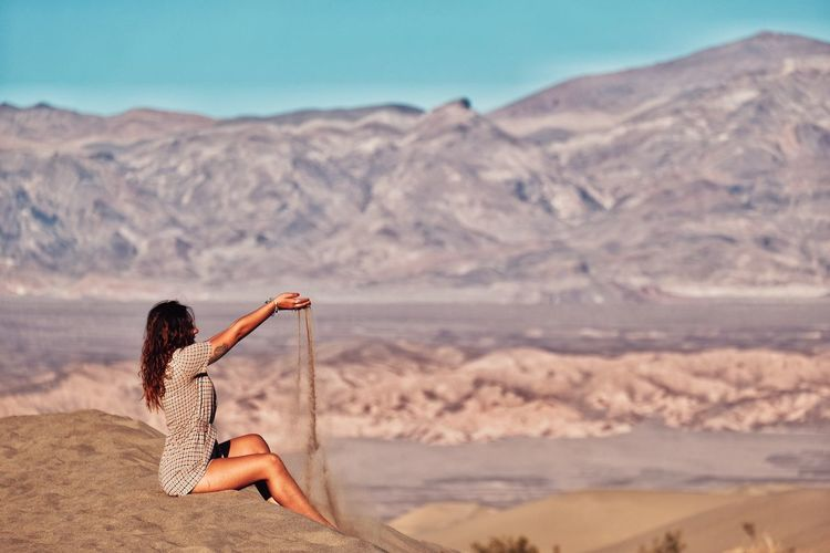 Side view of woman playing with sand dunes at desert