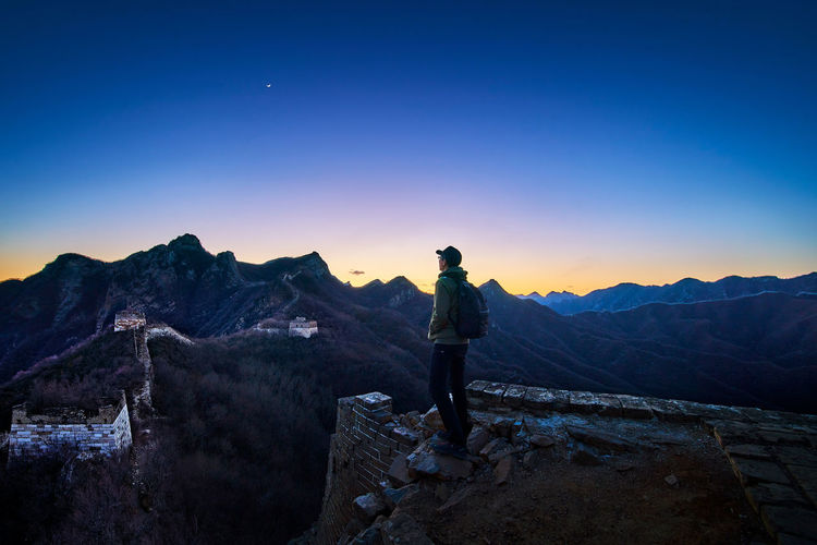 Side View Of Man Standing On Great Wall Of China During Sunset
