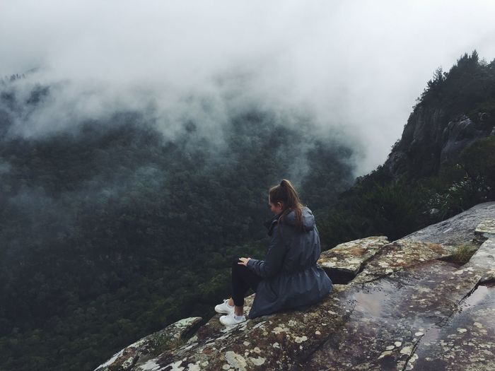 High angle view of young woman sitting on mountain during foggy weather
