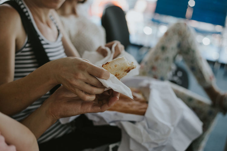 Adult Business Eating Fast Food Focus On Foreground Food Food And Drink Hand Holding Human Hand Hungry Incidental People Indoors  Lifestyles Midsection Paper Real People Restaurant Selective Focus Snack Take Out Food Unhealthy Eating Women