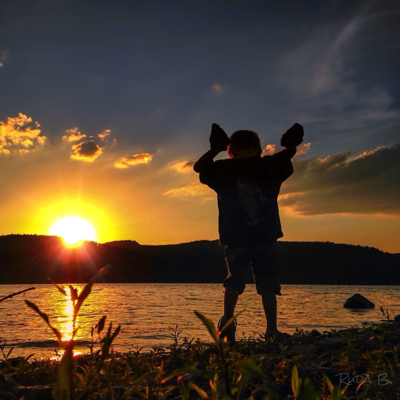 Boy Standing At Lakeshore During Sunset