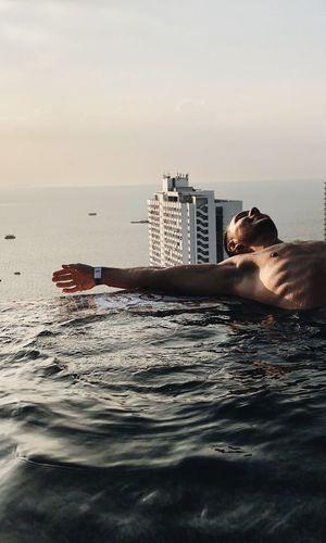 Man swimming in pool by sea against sky