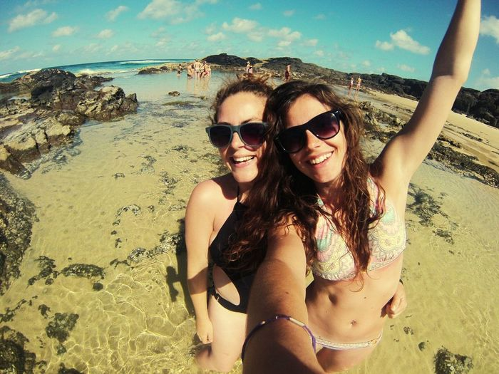 Smiling Young Women Taking Selfies At Beach Against Sky