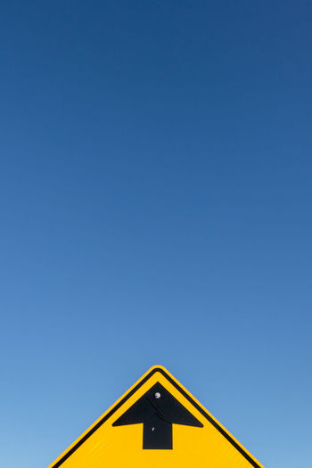 Low Angle View Of Arrow Sign Against Clear Sky