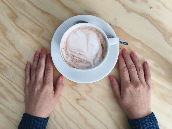 Cropped hands by coffee cup on table
