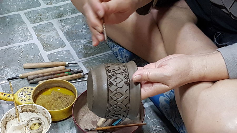 High angle view of woman decorating pottery