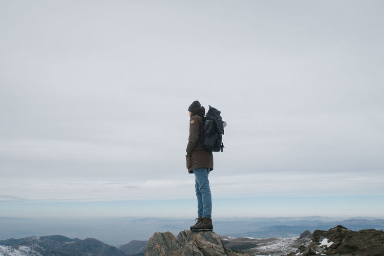 Male hiker standing on mountain against sky